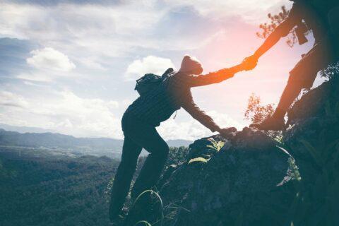 Freunde helfen einander beim Bergwandern. Gemeinsam erreichen wir das Ziel einer nachhaltigen Unternehmenspraxis.