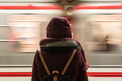 Frau vor einfahrendem Zug. Anfahrt zur Nachhaltigkeitskonferenz der GfaW.